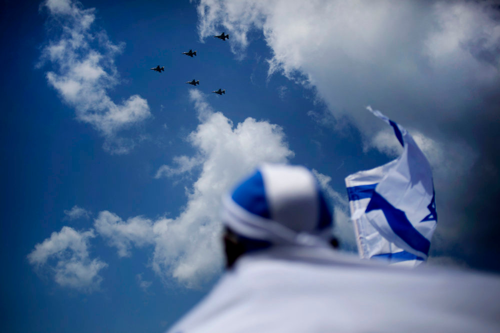 . An African migrant worker holds Israeli flags during an air show on Independence Day in Tel Aviv, Tuesday, April 16, 2013. Israel is celebrating its annual Independence Day, marking 65 years since the founding of the state in 1948. (AP Photo/Ariel Schalit)