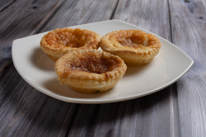 Three traditional bakewell puddings on a white plate side view