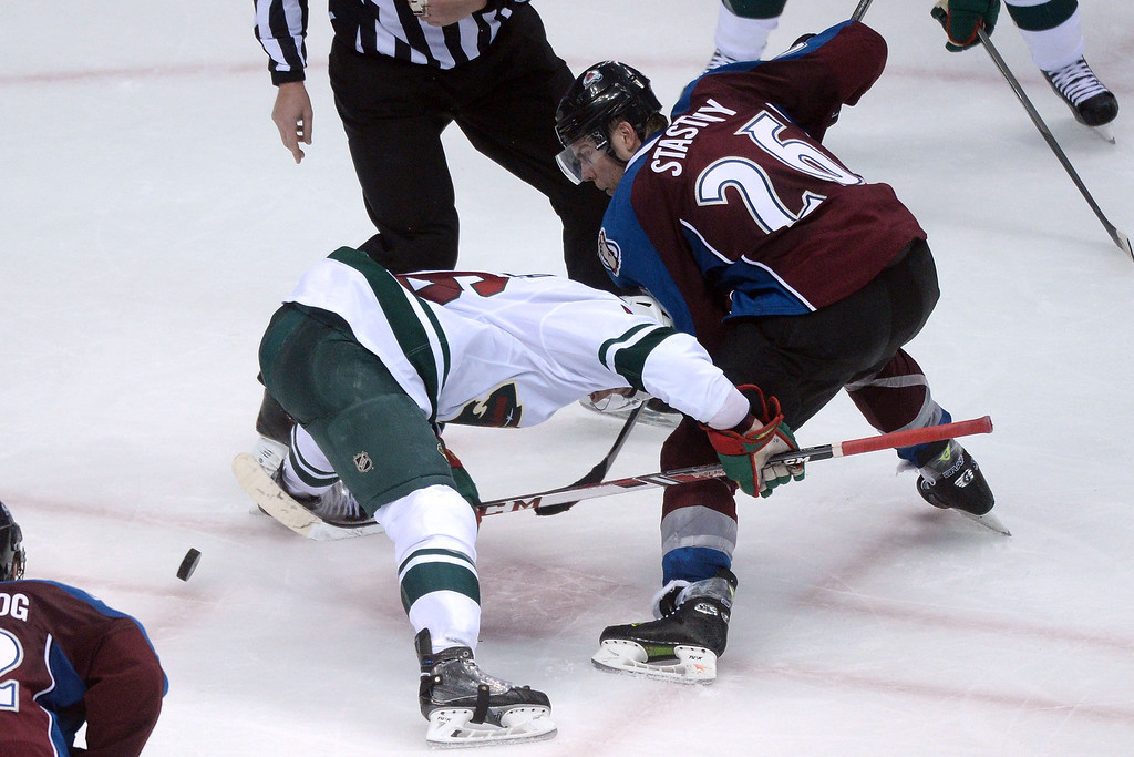. DENVER, CO - APRIL 26: Paul Stastny (26) of the Colorado Avalanche pokes the puck between the legs of Jared Spurgeon (46) of the Minnesota Wild during the third period. The Colorado Avalanche hosted the Minnesota Wild during game five of the first round of the NHL Stanley Cup Playoffs at the Pepsi Center on Saturday, April 26, 2014. (Photo by Karl Gehring/The Denver Post)