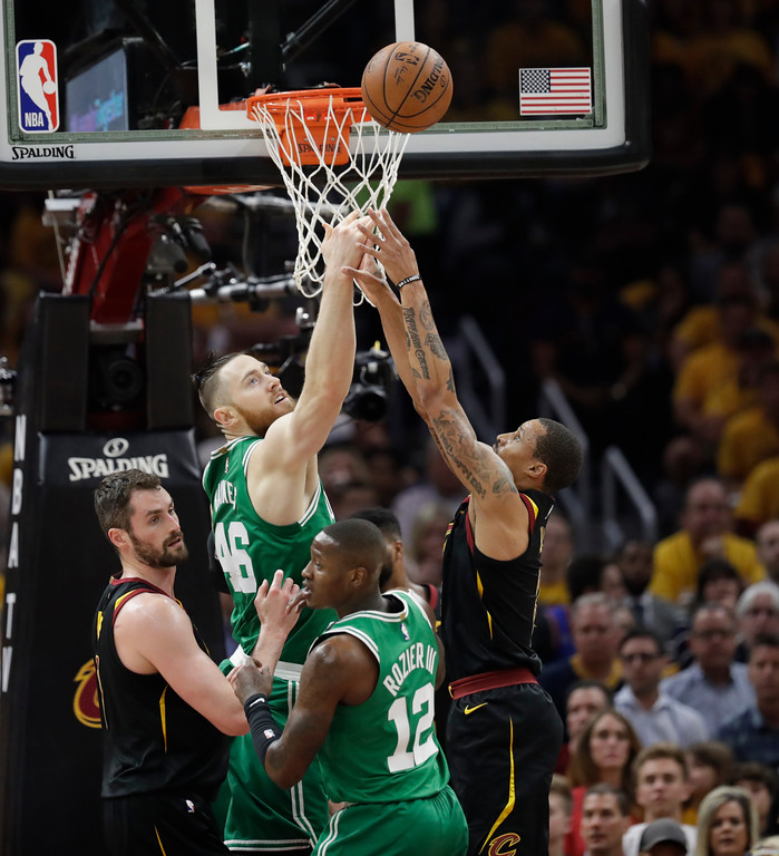 . Boston Celtics\' Aron Baynes (46), from Australia, and Cleveland Cavaliers\' George Hill, right, go for a rebound as Cavaliers\' Kevin Love, left, and Celtics\' Terry Rozier (12) stand by in the first half of Game 3 of the NBA basketball Eastern Conference finals, Saturday, May 19, 2018, in Cleveland. (AP Photo/Tony Dejak)