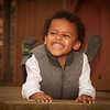 Portrait image of a young African American boy looking at the camera smiling and laughing.