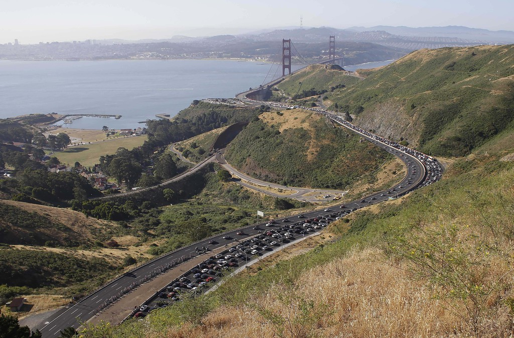 . The peloton, lower left, makes its way up Highway 101 with the Golden Gate Bridge in the background during the final stage of the Tour of California cycling race on Sunday, May 19, 2013, in Sausalito, Calif.  The final stage began in San Francisco and ended in Santa Rosa, Calif. (AP Photo/Eric Risberg)