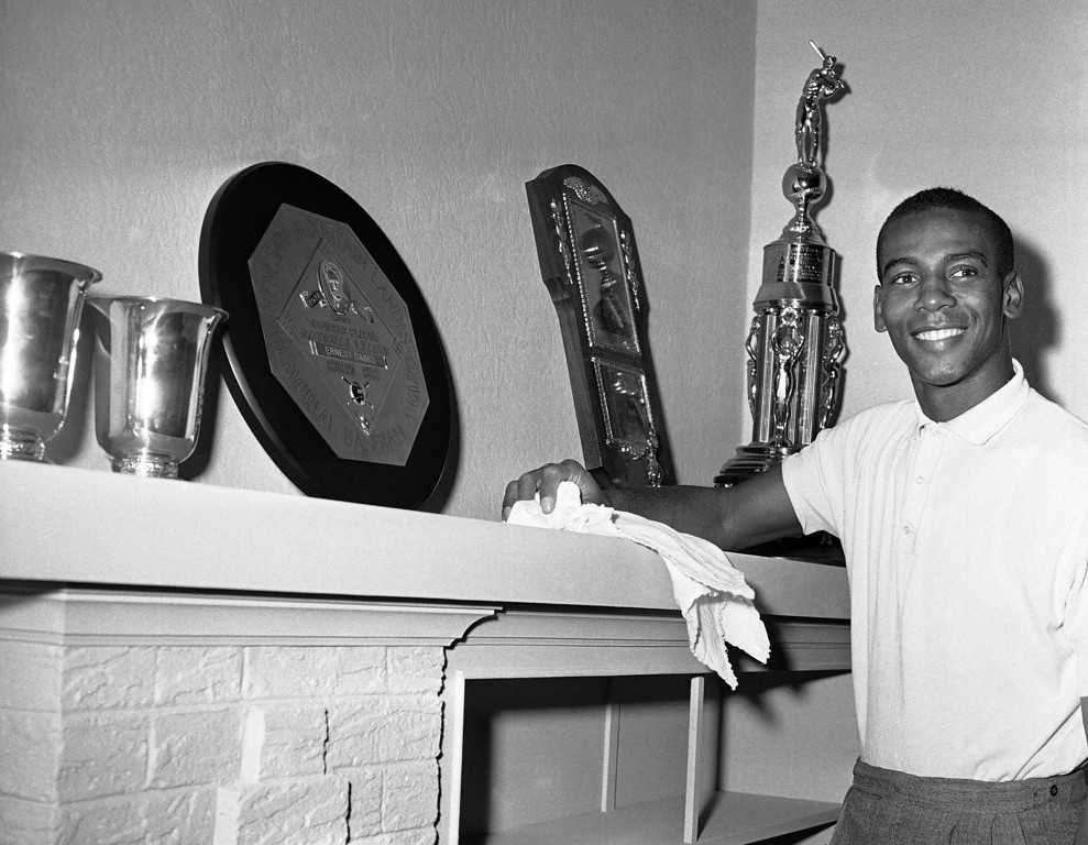 . FILE - In this Nov. 5, 1959, file photo, Chicago Cubs shortstop Ernie Banks, who won the National League most valuable player award for the second successive year, makes room on his mantle for a new trophy in Chicago. The round plaque in center is the 1958 Most Valuable player award. The Cubs announced Friday night, Jan. 23, 2015, that Banks had died. The team did not provide any further details. Banks was 83. (AP Photo/CEK, File)