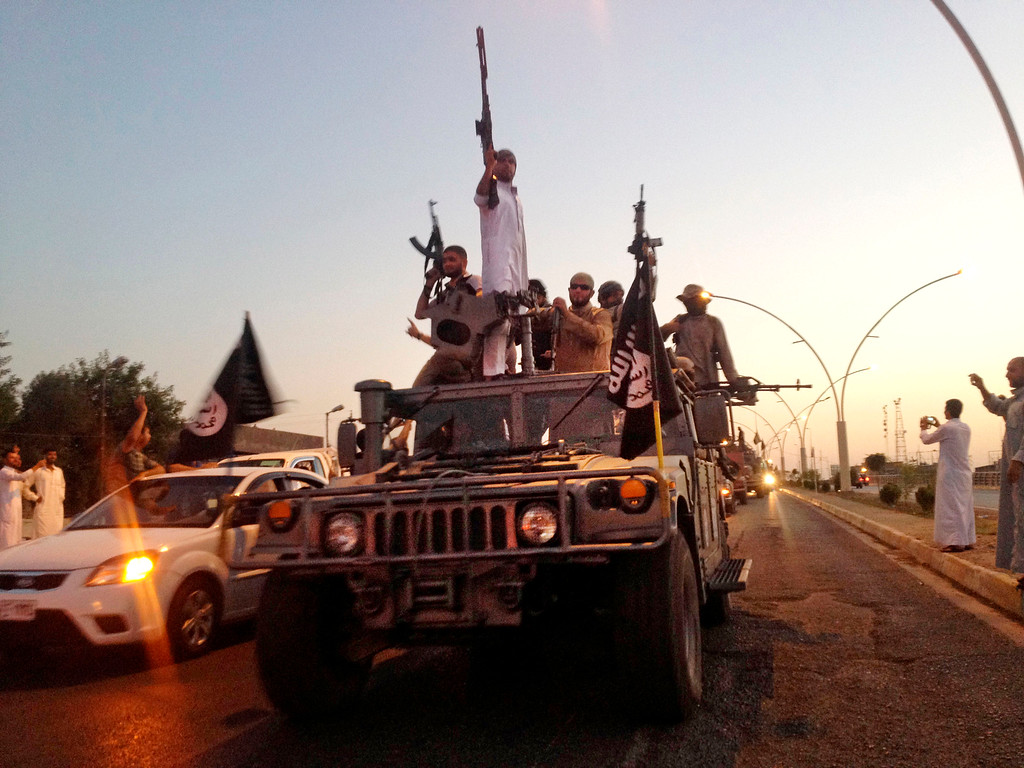 . In this photo taken Monday, June 23, 2014, fighters from the Islamic State group parade in a commandeered Iraqi security forces armored vehicle down a main road at the northern city of Mosul, Iraq.  (AP Photo/File)