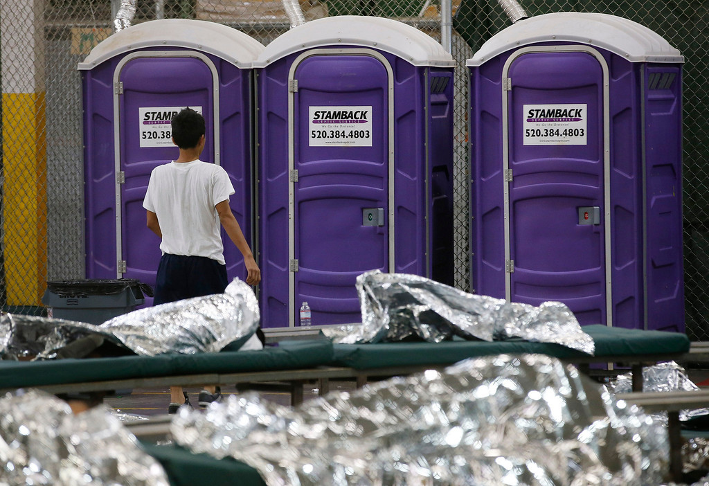 . A young boy walks over to use the toilet while in his holding area where hundreds of mostly Central American immigrant children are being processed and held at the U.S. Customs and Border Protection Nogales Placement Center on Wednesday, June 18, 2014, in Nogales, Ariz.   (AP Photo/Ross D. Franklin, Pool)