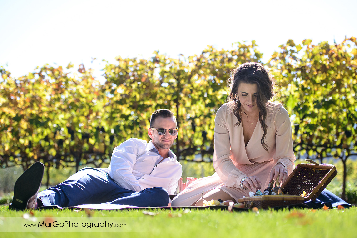 man in white shirt and blue pants and woman in pink dress having picnic during Napa Valley engagement session at Frank Family Vineyards in Calistoga
