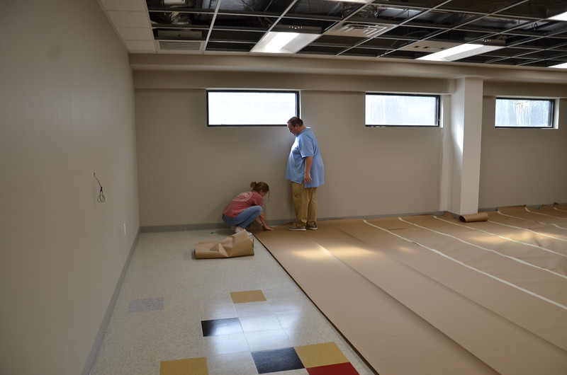 "Rene Mouton and Brad Helm ""paper"" the new floor before furniture is moved."