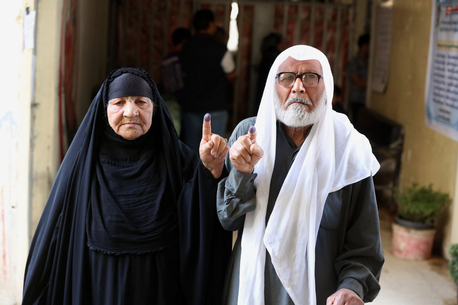 Description of . A man and his wife show their inked fingers after casting their votes for parliamentary elections at a polling in Baghdad, Iraq, Wednesday, April 30, 2014. Iraq is holding its third parliamentary elections since the U.S.-led invasion that toppled dictator Saddam Hussein. More than 22 million voters are eligible to cast their ballots to choose 328 lawmakers out of more than 9,000 candidates. (AP Photo/ Karim Kadim)