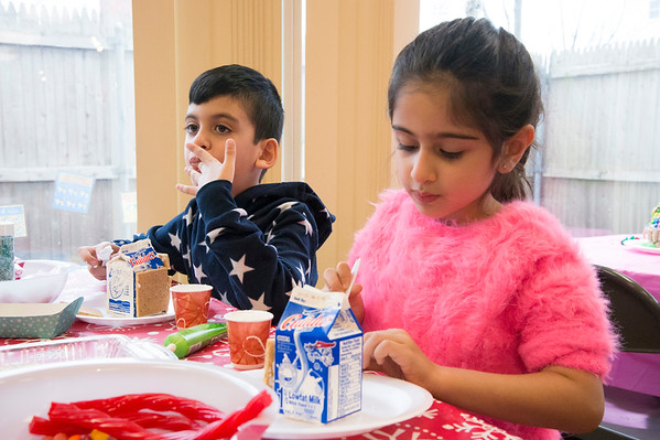 12/27/19 Wesley Bunnell | StaffrrGingerbread house making took place on Friday afternoon at the New Britain Youth Museum in New Britain. Fahad Akberzai, age 7, licks up some excess frosting as his sister Hira, age 5, works on her house.