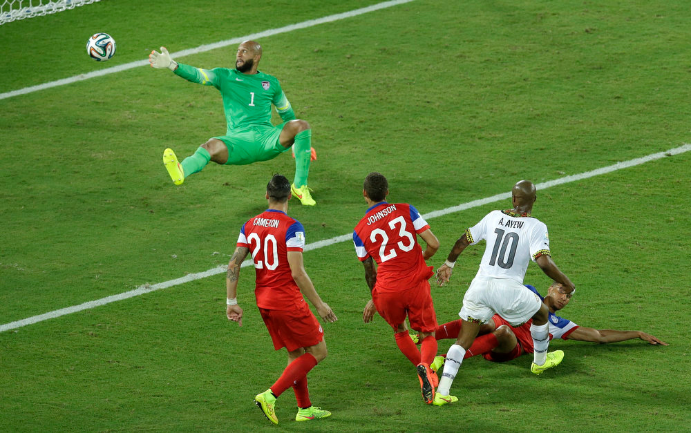 Description of . Ghana's Andre Ayew (10), right, scores his side's first goal past United States' goalkeeper Tim Howard, top, during the group G World Cup soccer match between Ghana and the United States at the Arena das Dunas in Natal, Brazil, Monday, June 16, 2014. (AP Photo/Hassan Ammar)