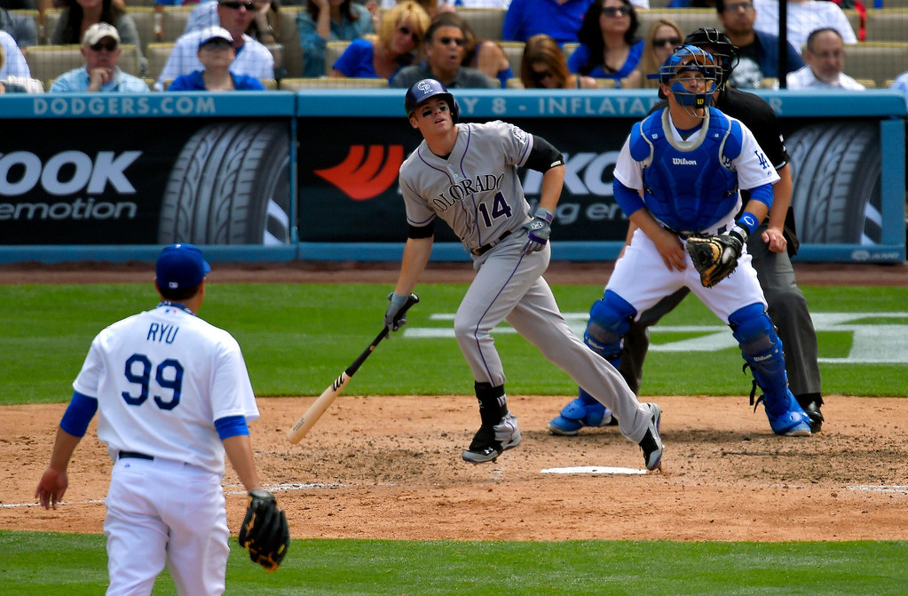. Colorado Rockies\' Josh Rutledge, center, hits a three-run home run as Los Angeles Dodgers starting pitcher Ryu Hyun-Jin, left, of South Korea, and catcher Tim Federowicz look on during the sixth inning of a baseball game, Sunday, April 27, 2014, in Los Angeles. (AP Photo/Mark J. Terrill)