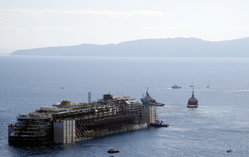 . The Costa Concordia cruise ship is towed away from the tiny Tuscan island of Isola del Giglio, Italy, Wednesday, July 23, 2014.  After more than two years since it slammed into a reef along the coastline of Isola del Giglio the wreck has begun its last journey, to the Italian port of Genoa, where it will be scrapped. 32 people died in the incident. (AP Photo/Gregorio Borgia)