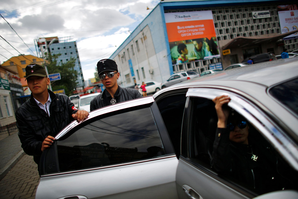 . Members of the Mongolian neo-Nazi group Tsagaan Khass leave their headquarters in Ulan Bator June 23, 2013. The group has rebranded itself as an environmentalist organisation fighting pollution by foreign-owned mines, seeking legitimacy as it sends Swastika-wearing members to check mining permits.Over the past years, ultra-nationalist groups have expanded in the country and among those garnering attention is Tsagaan Khass, which has recently shifted its focus from activities such as attacks on women it accuses of consorting with foreign men to environmental issues, with the stated goal of protecting Mongolia from foreign mining interests. This ultra-nationalist group was founded in the 1990s and currently has 100-plus members. Picture taken June 23, 2013.  REUTERS/Carlos Barria