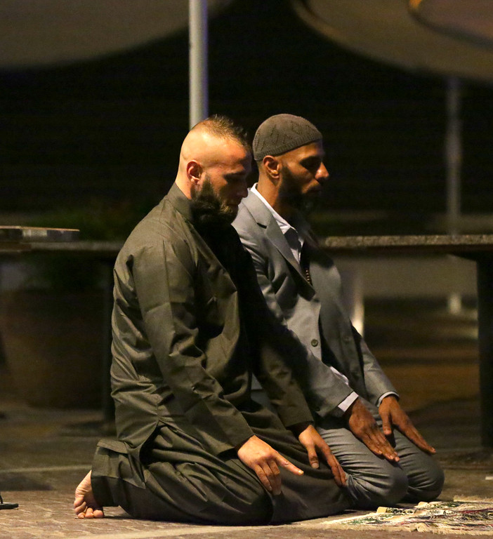. Sam Tiger right, and Abdulrahman El-Lawn perform  prayers  after a cafe siege in the central business district of Sydney , Australia, Tuesday, Dec. 16, 2014. This was their first prayer of the morning and prayed for peace and to bring comfort upon those affected especially  the hostages and their families. They both made a second prayer  directed towards Muslims to make the aftermath a peaceful one. (AP Photo/Glenn Nicholls)