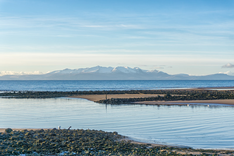 Looking over from the Irvine redeveloped Harbourside across the old harbour to the snow covered Isle of Arran in the far frozen hazy distance.on a -6 day in January.