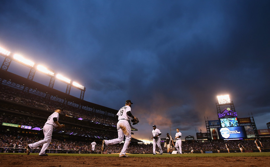 . DENVER, CO - MAY 02:  The Colorado Rockies take the field in the fourth inning against the New York Mets as the sun sets at Coors Field on May 2, 2014 in Denver, Colorado.  (Photo by Doug Pensinger/Getty Images)