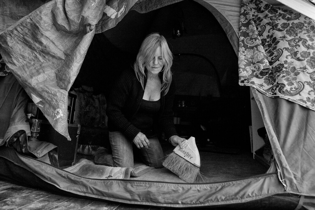 . Dorothy Edwards cleans up her tent, which she set up in a secluded area along the 210 Freeway in Pasadena, California.  (Photos by Sarah Reingewirtz / Pasadena Star-News)
