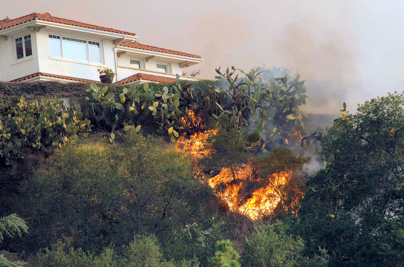 . A fast moving wildfire makes it way up a hill towards a house in the hills just north of the San Gabriel Valley community of Glendora, Calif. on Thursday, Jan 16, 2014. Southern California authorities have ordered the evacuation of homes at the edge of a fast-moving wildfire burning in the dangerously dry foothills of the San Gabriel Mountains. (AP Photo/Nick Ut)