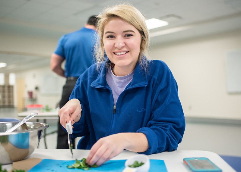Student Carlie Allen chops some cilantro during the Cooking Essentials 101 Class.  Sign up for Cooking Essentials 101 at the Texas A&M University-Corpus Christi Recreational Sports office located in the Dugan Wellness Center.