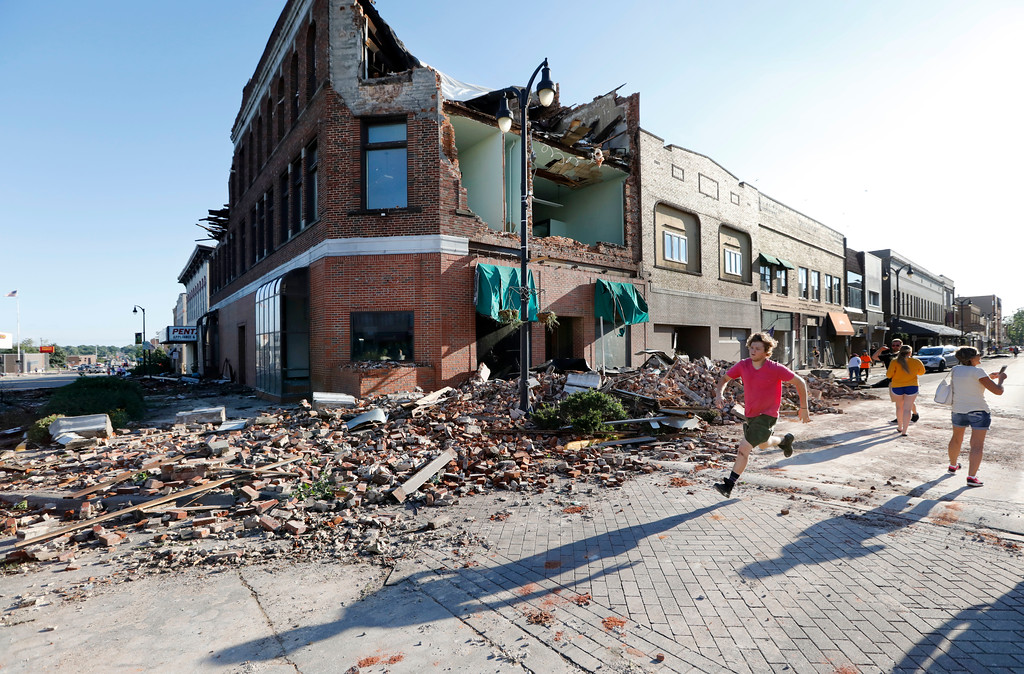 . A local resident runs past a tornado-damaged building on Main Street, Thursday, July 19, 2018, in Marshalltown, Iowa. Several buildings were damaged by a tornado in the main business district in town including the historic courthouse. (AP Photo/Charlie Neibergall)