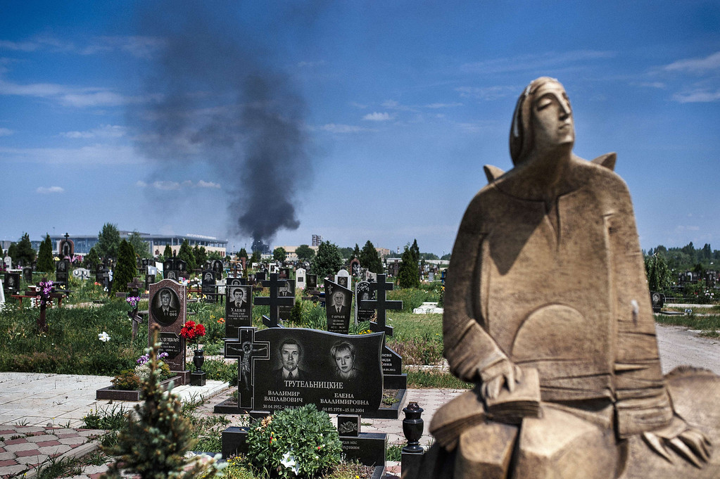 . Black smoke billows from Donetsk international airport, seen behind a cemetery, during heavy gun battle between the Ukrainian army and pro-Russian militants in the eastern Ukrainian city of Donetsk on May 26, 2014. Ukraine scrambled fighter jets and combat helicopters to strike rebel gunmen who seized control of the main airport in the eastern city of Donetsk on May 26, triggering heavy gunbattles and Ukrainian combat helicopters hitting an airport terminal. The fierce confrontation erupted after Ukrainian oligarch Petro Poroshenko, who claimed victory in Sunday\'s crucial presidential election, vowed to press on with an offensive against pro-Russian separatists waging a bloody insurgency across the east.  DIMITAR DILKOFF/AFP/Getty Images