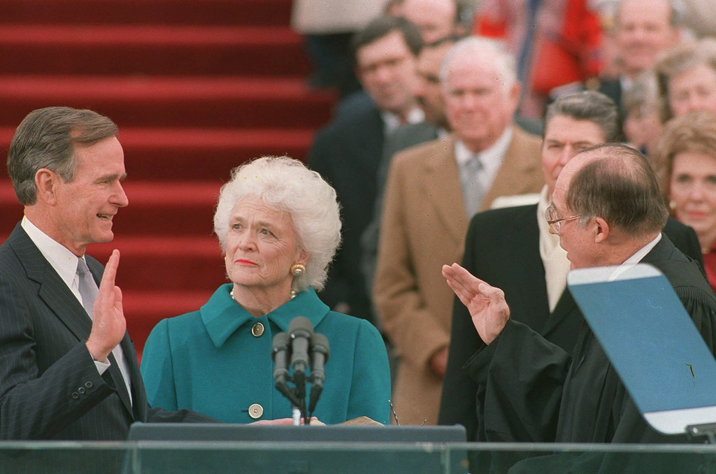 . President George Bush raises his right hand as he is sworn into office as the 41st president of the United States by Chief Justice William Rehnquist outside the west front of the Capitol on Jan. 20, 1989.  First lady Barbara Bush holds the bible for her husband.  Former President Reagan is in the background.  (AP Photo/Bob Daugherty)
