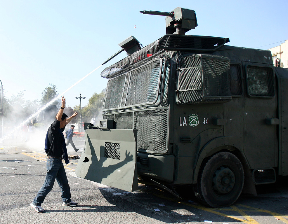. A demonstrator blocks a riot police vehicle spraying protesters with a water cannon during May Day rallies in Santiago May 1, 2008. REUTERS/Ivan Alvarado