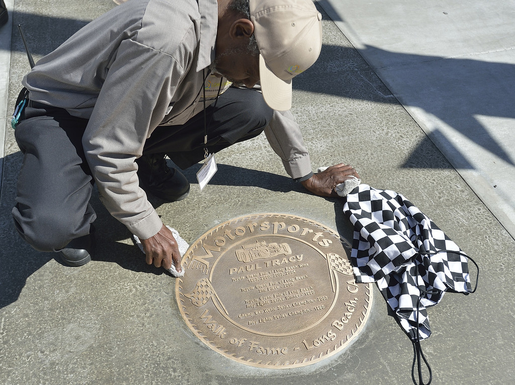 . LONG BEACH, CALIF. USA -- Hubert Moshay cleans a plaque before the start of the Long Beach (Calif.) Motorsports Grand Prix Walk of Fame induction ceremony on April 18, 2013. This year include Paul Tracy of Canada and Adrian Fernandez of Mexico. The annual Long Beach Motorsports Walk of Fame induction ceremony occurs in April of each year the Thursday before Toyota Grand Prix of LongBeach raceweekend. Photo by Jeff Gritchen / Los Angeles Newspaper Group