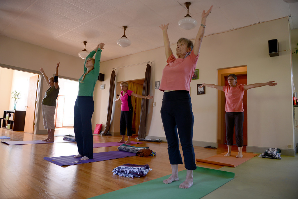 . Tania Barricklo-Daily Freeman Participants in a yoga class at Mudita Yoga in Kingston do some stretches at the start of class.