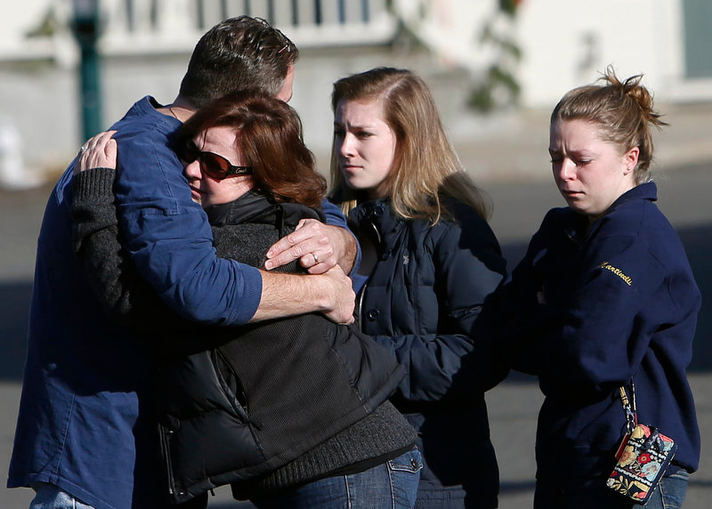 Description of . Mourners embrace outside Saint Rose of Lima Roman Catholic Church, Saturday, Dec. 15, 2012 in Newtown, Conn.  The massacre of 26 children and adults at Sandy Hook Elementary school elicited horror and soul-searching around the world even as it raised more basic questions about why the gunman, 20-year-old Adam Lanza, would have been driven to such a crime and how he chose his victims.  (AP Photo/Jason DeCrow)