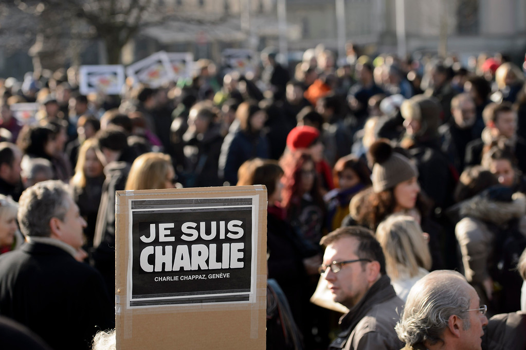 . People gather for a rally in solidarity with the killed Charlie Hebdo employees, Thursday, Jan. 8, 2015, in Geneva, Switzerland. Masked gunmen stormed on Wednesday the Paris offices of the satirical newspaper Charlie Hebdo, killing 12 people, including the paper\'s editor. (AP Photo/Keystone,Martial Trezzini)