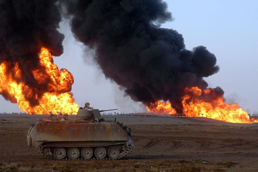 . An armored U.S. military vehicle passes near a burning oil pipeline on the outskirts of Fallujah, Iraq, Wednesday, Nov. 10, 2004. Insurgents set off the fire using rocket-propelled grenades Tuesday night. (AP Photo/Asaad Mohessin)