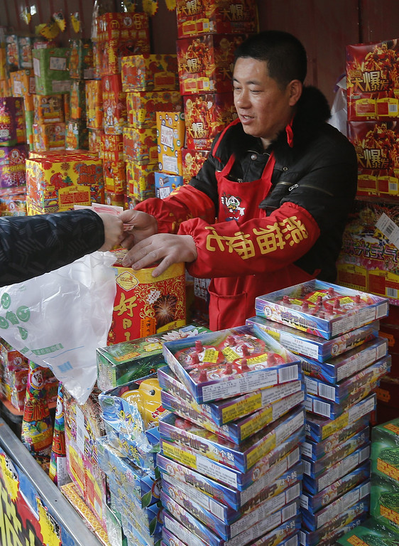 . A vendor selling fireworks and firecrackers receives payment from a customer at a roadside stall in Beijing, China, 30 January 2014. Concerns over air pollution levels have led authorities to urge the public to lessen the use of fireworks in welcoming the Lunar New Year, or Year of the Horse, which officially starts on 31 January.  EPA/ROLEX DELA PENA