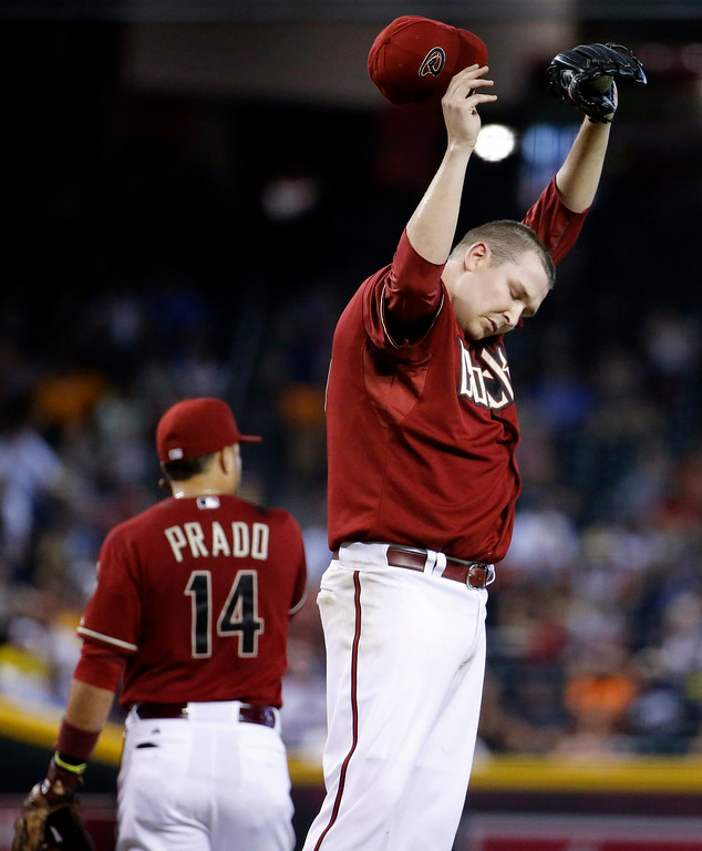 . Arizona Diamondbacks pitcher Trevor Cahill wipes his head during the fourth inning of a baseball game against the Detroit Tigers, Wednesday, July 23, 2014, in Phoenix. (AP Photo/Matt York)