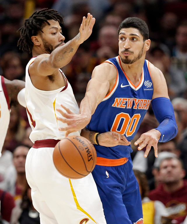 . New York Knicks\' Enes Kanter (00) passes against Cleveland Cavaliers\' Derrick Rose (1) in the first half of an NBA basketball game, Sunday, Oct. 29, 2017, in Cleveland. (AP Photo/Tony Dejak)
