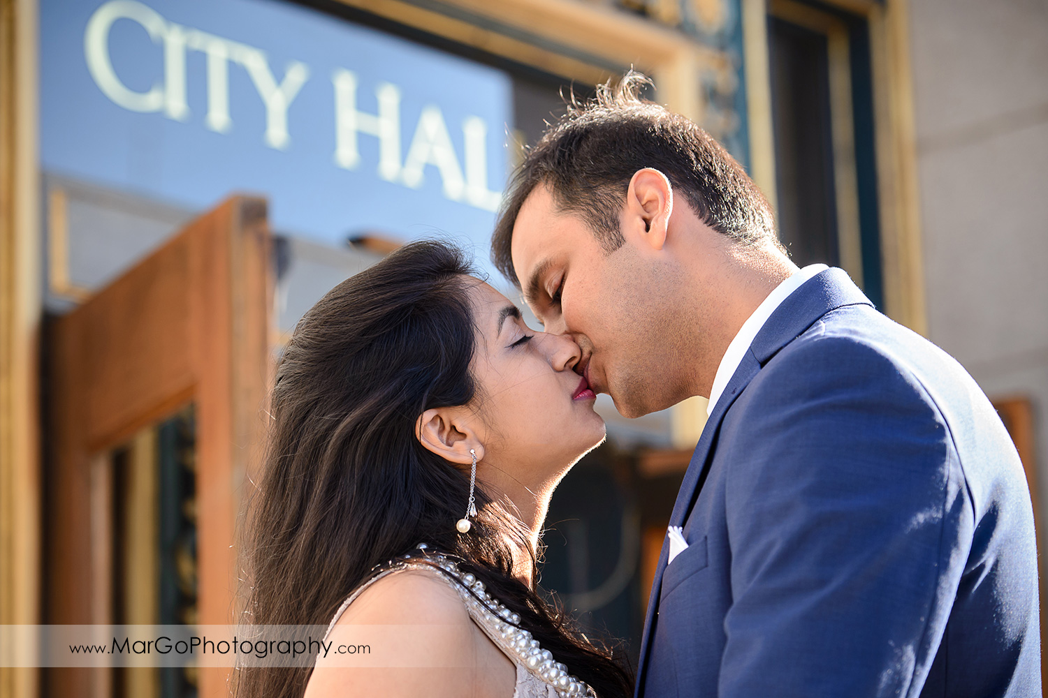 woman in beige dress and man in navy blue suit kissing in front of San Francisco City Hall entrance