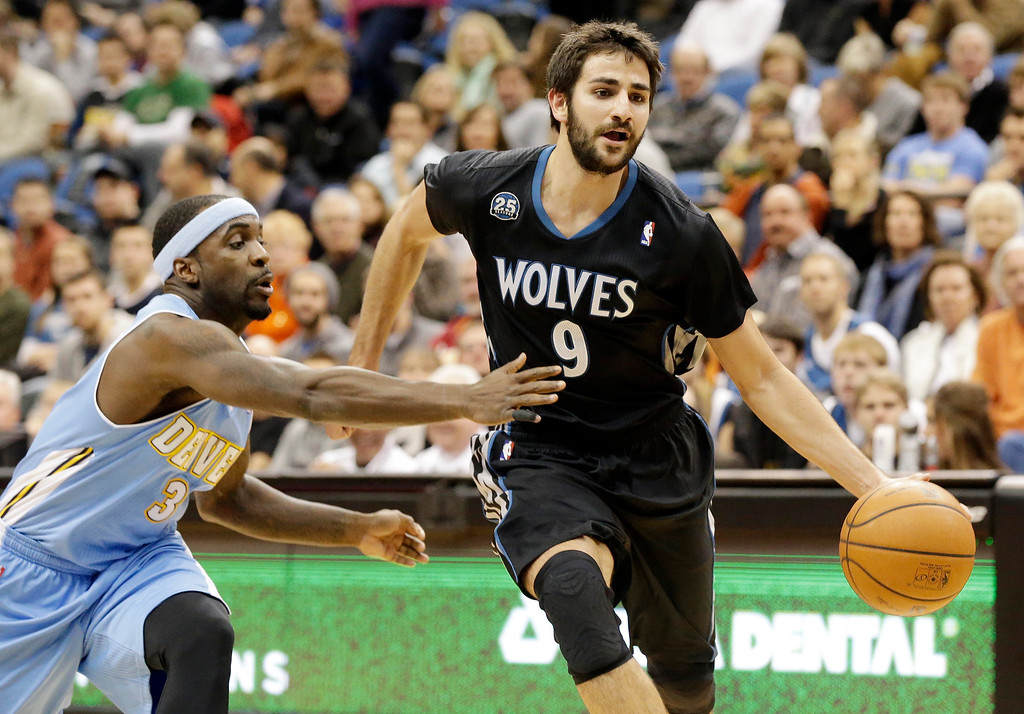 . Minnesota Timberwolves\' Ricky Rubio, right, of Spain, drives around Denver Nuggets\' Ty Lawson in the first quarter of an NBA basketball game on Wednesday, Nov. 27, 2013, in Minneapolis. (AP Photo/Jim Mone)