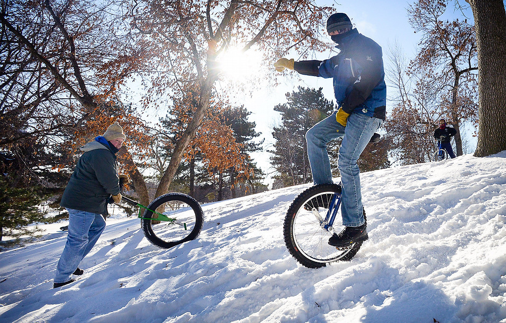 . Tim Lee of Eagan, left, watches as his son Bruce, 15, heads down the hill. (Pioneer Press: Ben Garvin)