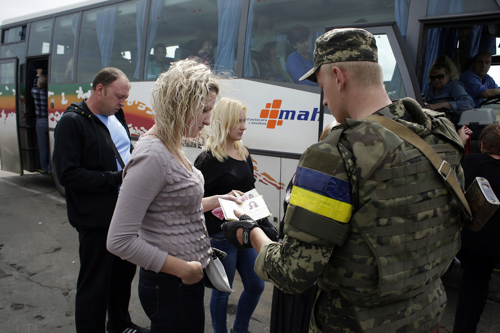. A Ukrainian soldier controls passengers before they get on a bus at a checkpoint controlled by Ukrainian forces on September 10, 2014, near the small eastern Ukrainian city of Slavyanoserbsk, in the Lugansk region.  AFP PHOTO/ ANATOLII STEPANOVANATOLII STEPANOV/AFP/Getty Images