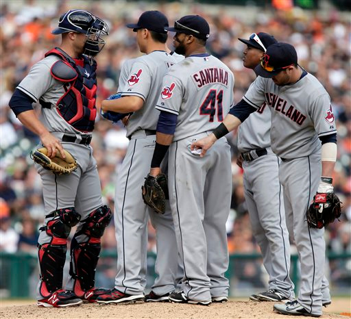 . Cleveland Indians\' Jason Kipnis, right, tucks in the back pocket liner of Carlos Santana\'s (41) pants during a visit to the mound to talk to C.C. Lee and catcher Rich Hill in the seventh inning of a baseball game against the Detroit Tigers, Sunday, Sept. 14, 2014, in Detroit. The Tigers defeated the Indians 6-4. (AP Photo/Duane Burleson)