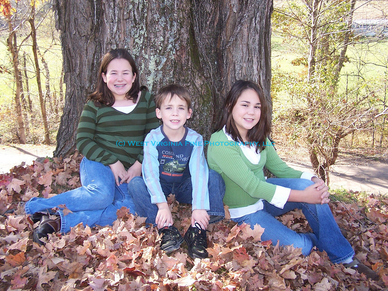 Lindsey, Nathan, and Chelsey in the leaves.