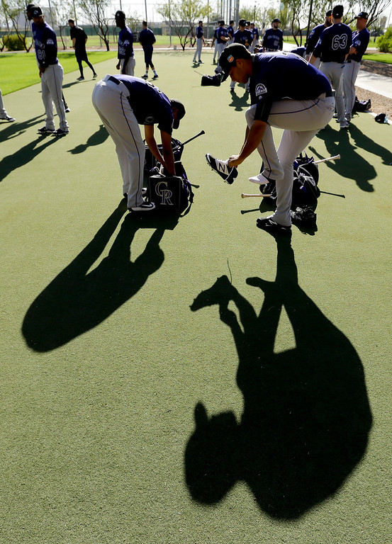 . Colorado Rockies starting pitcher German Marquez, left, and relief pitcher Carlos Estevez get ready for spring training baseball practice in Scottsdale, Ariz., Monday, Feb. 22, 2016. (AP Photo/Chris Carlson)