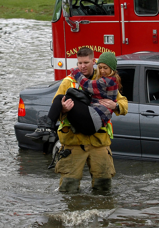 . San Bernardino City firefighter paramedic Corie Lynch rescues Maegen Pettit, 25, of Ventura, from a vehicle that got stuck in the flooded intersecion of Hosptiality Lane and E Street in San Bernardino March 17, 2012.  The flooding was caused by a drain overflowing due to an extreme deluge of rain.  (Photo by Gabriel Luis Acosta/The Sun)