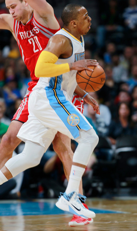 . Denver Nuggets guard Randy Foye, front, runs into Houston Rockets forward Donatas Motiejunas, of Lithuania, in the first quarter of an NBA basketball game in Denver on Wednesday, April 9, 2014. (AP Photo/David Zalubowski)