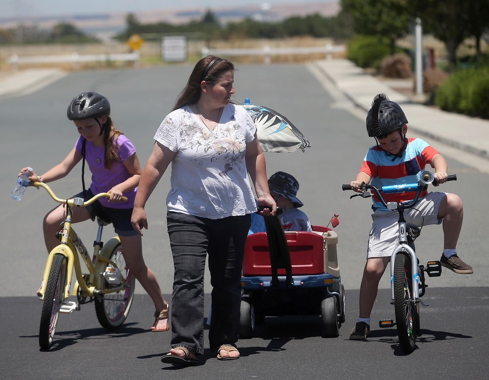 . Kristi Ouimet pulls her son Matthew, 3, as they had back from a local park with his sister Molly, 11, and brother Patrick, 9, in Antioch, Calif., on Thursday, May 22, 2014. (Jane Tyska/Bay Area News Group)