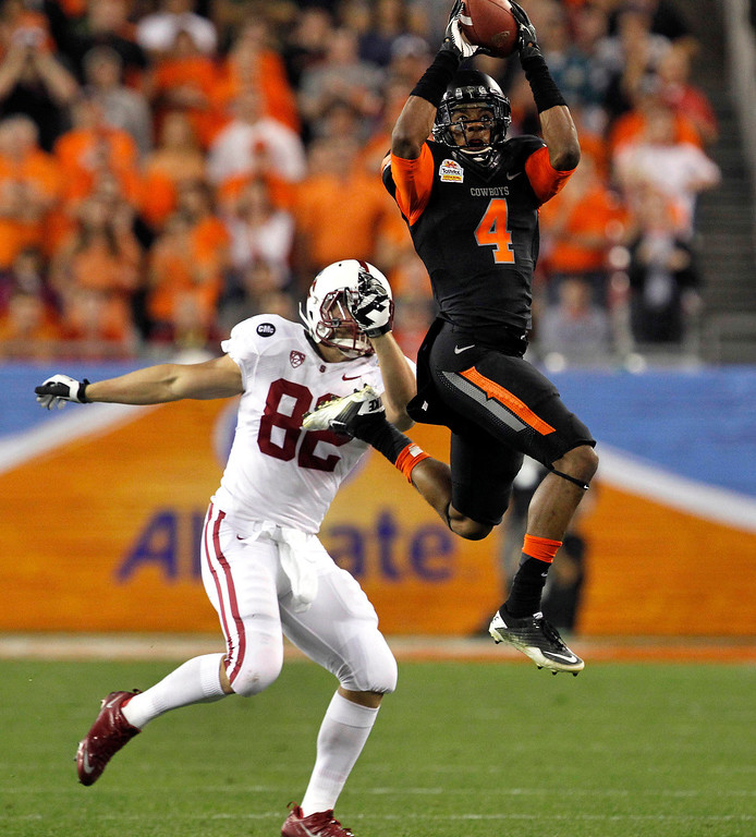 . In this Jan. 2, 2012, file photo, Oklahoma State cornerback Justin Gilbert (4) intercepts a pass intended for Stanford tight end Coby Fleener (82) during the first half of the Fiesta Bowl NCAA college football game in Glendale, Ariz. Gilbert was picked #8 overall by the Cleveland Browns during the first round. (AP Photo/Ross D. Franklin, File)