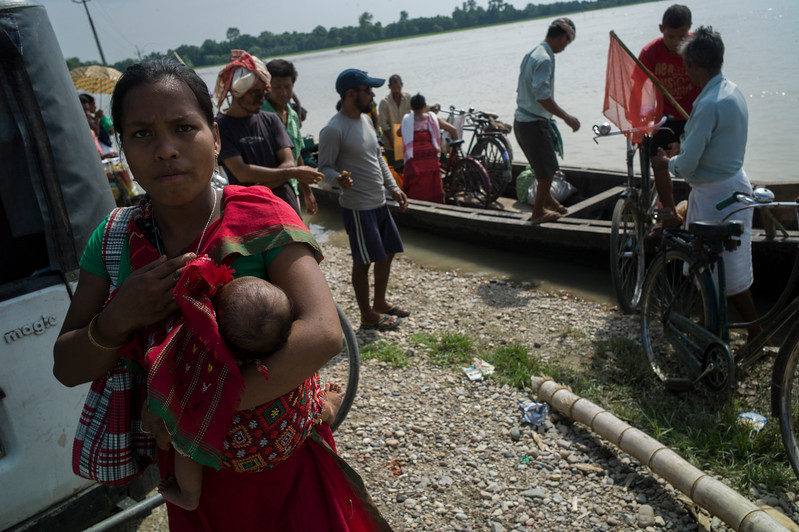 Dhemanji, Assam, India August,2014:   Men and women from Narayanpur village commute by boats due to floods. Poverty due to displacements because of  floods is also a factor for early marriages.   Series on early marriages in Assam, India for Al Jazeera America.       Photo:  Sami Siva