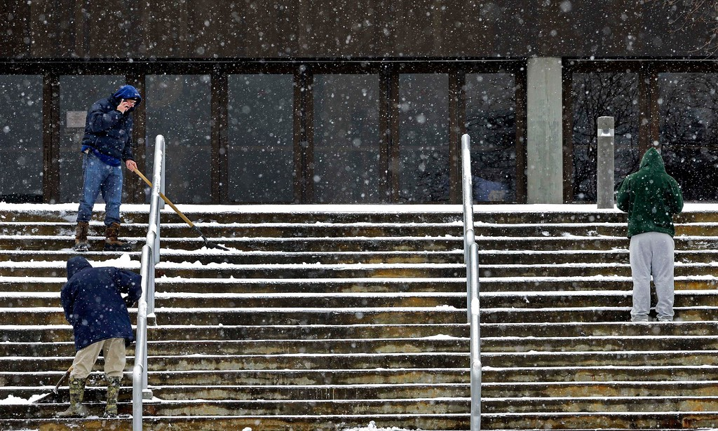. Workers shovel snow and sleet from the stairs outside the Dean E. Smith Center in preparation for tonight\'s NCAA basketball game between North Carolina and North Carolina State in Chapel Hill, N.C., Saturday, Jan. 7, 2017. (AP Photo/Gerry Broome)