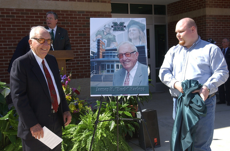 "Businessman and philanthropist James H. ""Buck"" Harless of Gilbert, W.Va., joined Marshall University's Board of Governors in dedicating the Harless Dining Hall on MU's Huntington campus March 10, 2004. Here he unveils a commemorative poster."