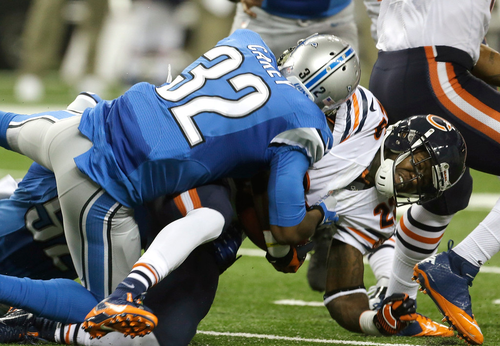 . Chicago Bears running back Matt Forte (22) is stopped by Detroit Lions strong safety Don Carey (32) during the first quarter of an NFL football game at Ford Field in Detroit, Sunday, Sept. 29, 2013. (AP Photo/Carlos Osorio)